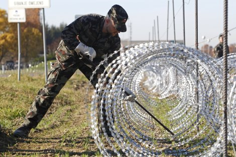 A Slovenian soldier sets up barbed wire barriers in the village Gibina